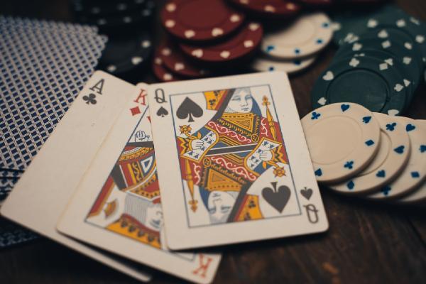 Drei Spielkarten neben Spielchips auf einem Tisch